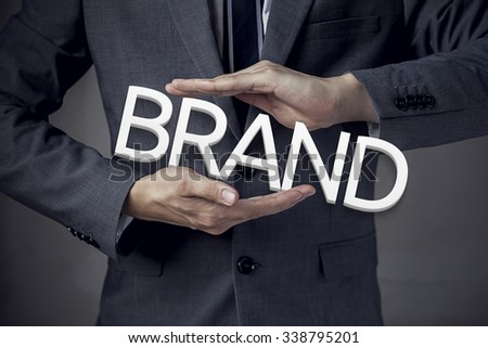 """Businessman in suit with two hands in position to protect the word """"BRAND"""" (focus on hand, blur out the suit)."""