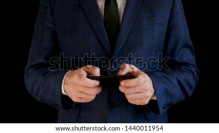 Businessman in suit works with a smartphone, touches the touch screen of the phone on a black background.