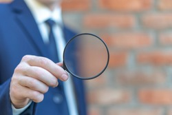 Businessman in suitcase hold magnifying glass on red brick wall background. Magnification Search Business Technology Concept.