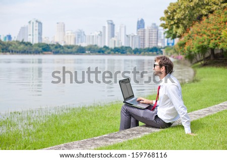 businessman in summer park (working in green environment)