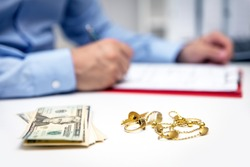 Businessman in the back, us dollars and gold jewellry in the front, disposal and selling