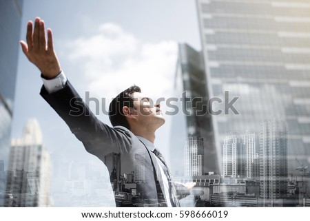Businessman in the city raising his arms, open palms, with face looking up - empowering, success and freedom concepts, double exposure effect