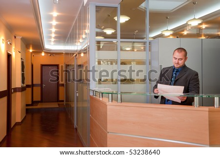 Businessman in the modern office looks at the document