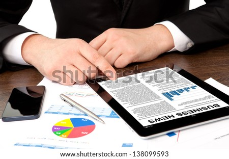 businessman in the office at the table watching business news on tablet computer screen