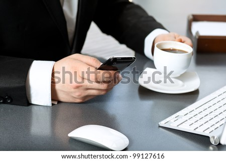 businessman in the office drinking coffee and talking on the touch tablet phone gadget.