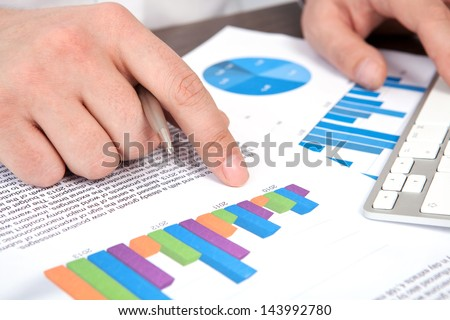 businessman in the office of the table points to the graphics