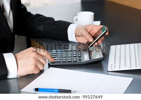 businessman in the office said on the calculator and talking on the touch tablet phone gadget.