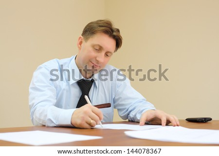Businessman in tie sits at table and signs documents in office.