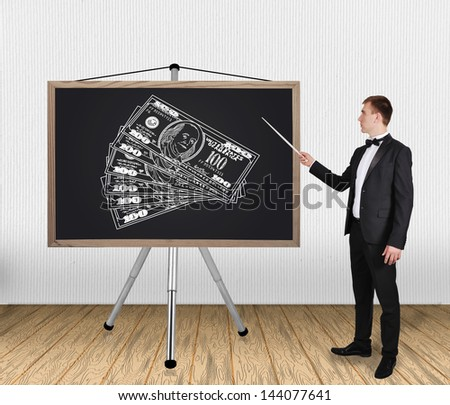 businessman in tuxedo pointing on blackboard with dollars