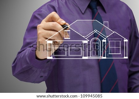 Businessman in violet shirt sketching house on screen