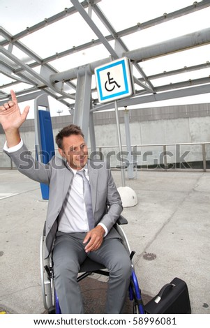 Businessman in wheelchair calling out for a taxi - stock photo
