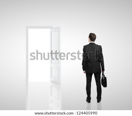 businessman in white room with doors open