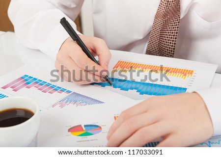 Businessman in white shirt and necktie analyzing graphs