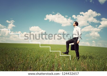 businessman in white shirt walks up the ladder in the green field