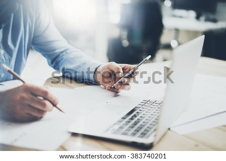 Businessman in workplace. Texting message smartphone and holding pencil hands. Generic design notebook wood table. Horizontal mockup, blurred background