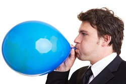 Businessman inflates a blue balloon