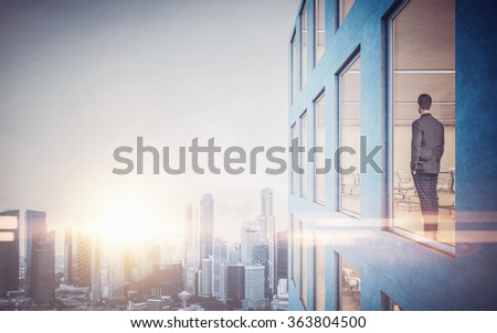 Businessman inside skyscraper, lookng at the city through  window. Horizontal