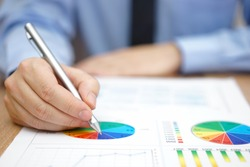 Businessman is analyzing business report with charts and diagrams
