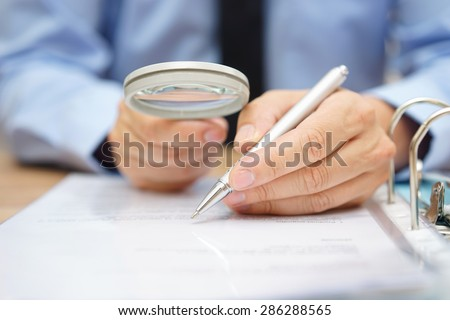 businessman is analyzing  through  magnifying glass contract and prices Foto stock ©