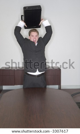 Businessman is angry and he\'s going to throw his briefcase in the conference room as he stands with a black suit on