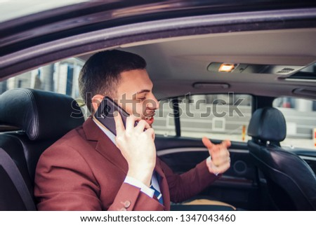Businessman is arguing with someone on mobile while he is driving in a limo car getting ready before a meeting