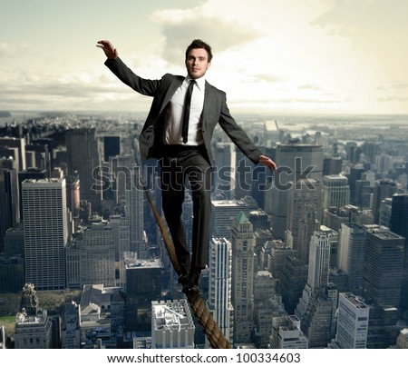 Businessman is balancing on a rope