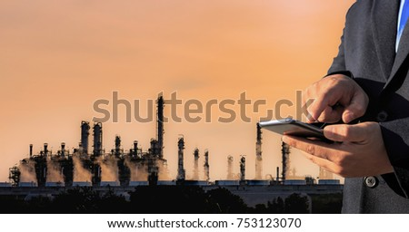 Businessman is holding smartphone with petrochemical oil refinery plant at night background