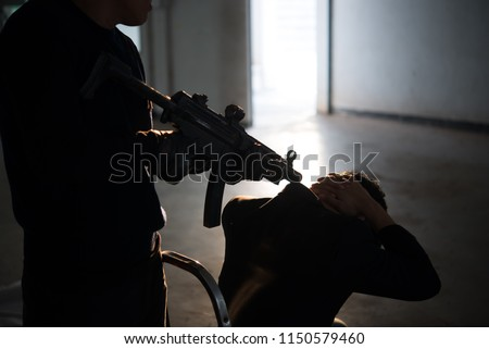 Businessman is hostage from bandit,Thailand people,Hostage of terrorist man concept,silhouette picture,sunset