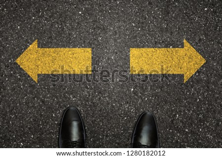 Businessman is looking down at his feet on a Asphalt road with choice arrows and navigation arrow on the surface. Concept of decision making and choices success in the future goal #1280182012