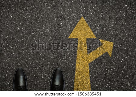 Businessman is looking down at his feet on a Asphalt road with choice arrows and navigation arrow on the surface. Concept of decision making and choices success in the future goal