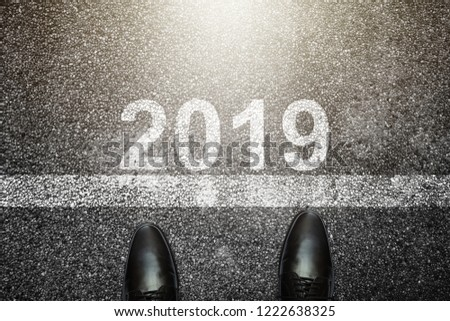 Businessman is looking down at his feet on a Asphalt road with 2019 number painted on the surface.Concept for success in the future goal and passing time. Happy new year