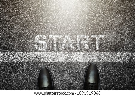 Businessman is looking down at his feet on a Asphalt road with start letters painted on the surface. An image of a milestone roadmap is a representation of success in the future goal #1091919068