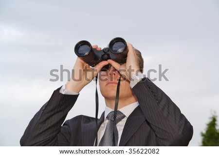 Businessman is looking through a pair of binoculars. Photo taken from below.
