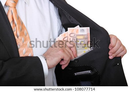 businessman is putting banknotes in his pocket