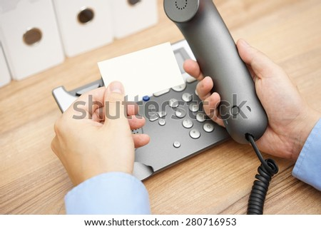 businessman is reading telephone number from business card to make a call #280716953