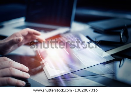 Businessman is researching fresh financial analytics on a screen of modern hi tech digital tablet. Male hands with futuristic device
