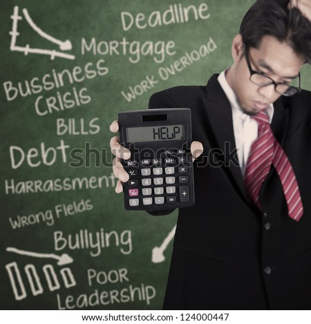 Businessman is showing calculator with HELP writing on it in front of blackboard - stock photo