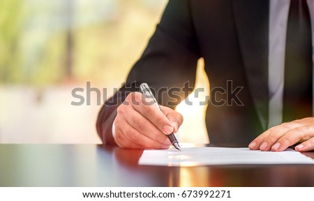 Businessman Is Signing A Legal Document In Office #673992271