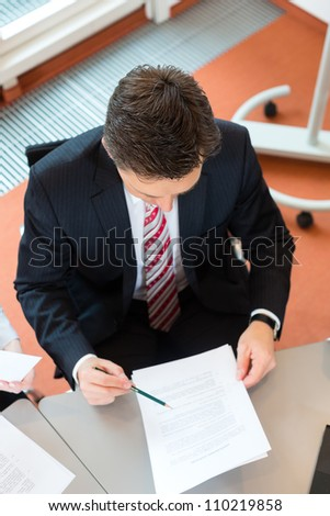 Businessman is sitting at office desk with a document