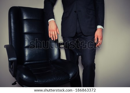 Businessman is standing by a large director\'s chair