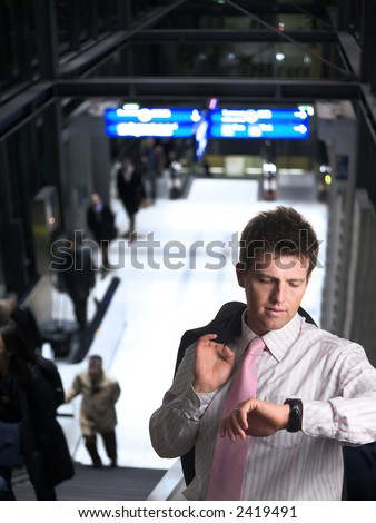 Businessman is standing on the escalator on a railwaystation or airport. He is checking the time on on his watch.