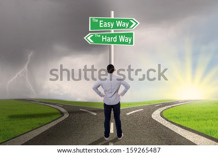 Businessman is standing on the road with sign of easy vs hard way