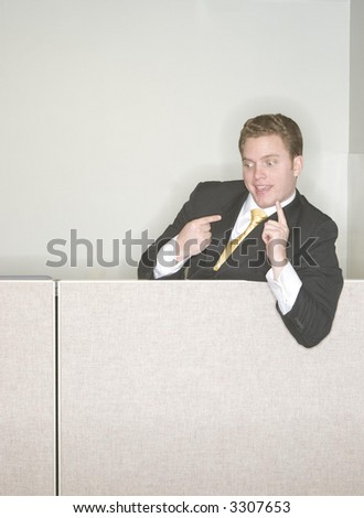 Businessman is taunting his coworkers from above at the top of his cubicle pointing his finger in the air in a sign of his success in the office