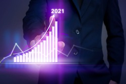 Businessman is touching growing graph on virtual screen with business strategy plan for 2021