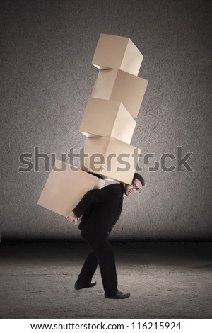 Businessman is trying to balance plenty of boxes that he is carrying