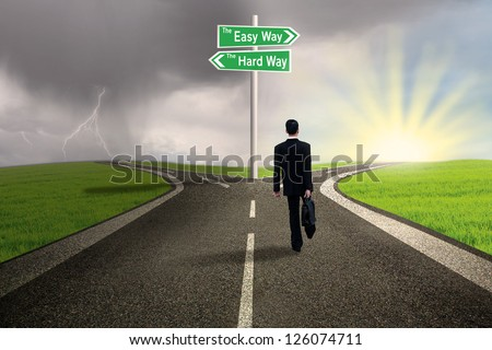 Businessman is walking on the easy way lane with stormy background