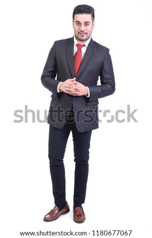 Businessman isolated in white background. Handsome young indian businessman in suit portrait, interlock fingers. Full length shot.
