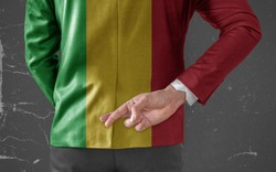 Businessman Jacket with Flag of Mali with his fingers crossed behind his back