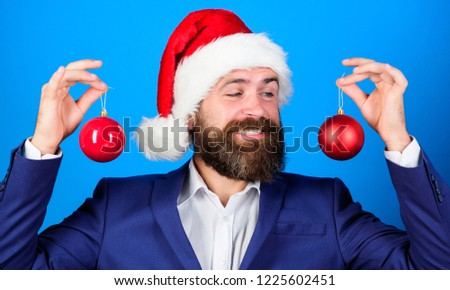Businessman join christmas celebration. Santa hold christmas ball decoration. Merry christmas. Christmas atmosphere spread around. Holidays meant for fun. Man bearded wear formal suit and santa hat.