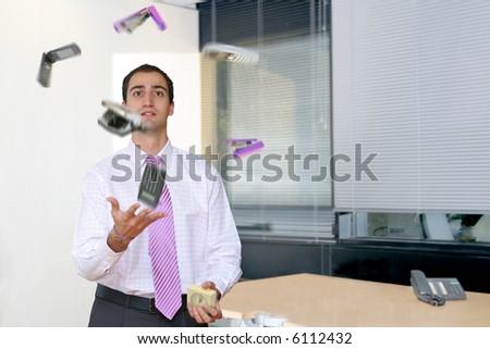 Businessman juggling desk items, left-hand-side of an office.